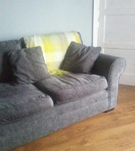 Grey sofa with yellow checked throw.