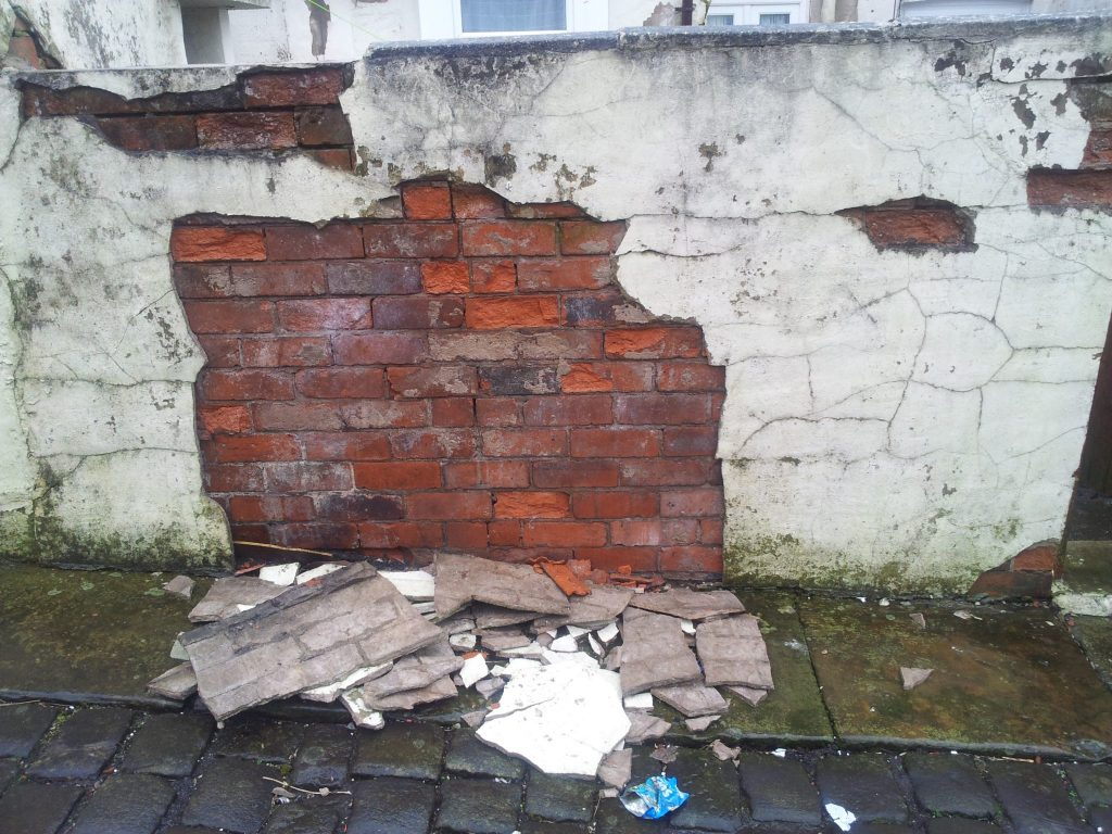 Poorly maintained wall with blown render.