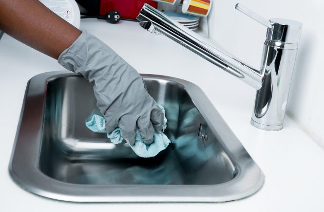 Gloved hand cleaning a sink - spring cleaning the blog
