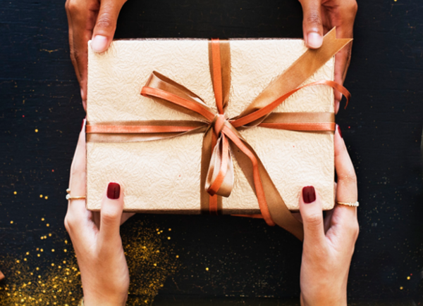 Hands giving and receiving a present | TopCashback new member offers