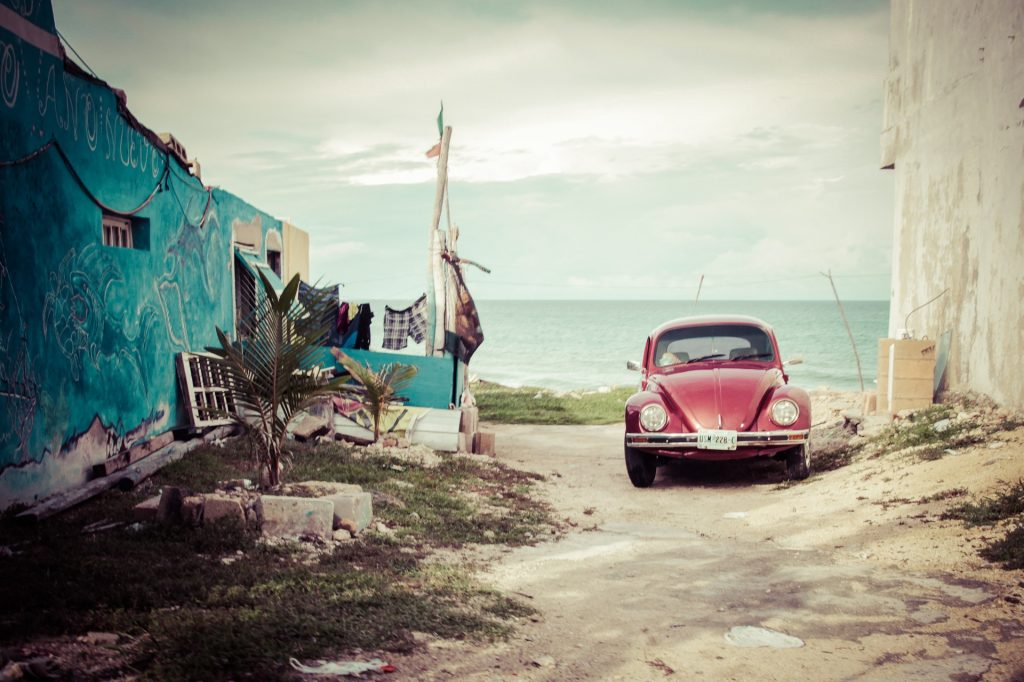 Red VW Beetle by beach - How to save money when purchasing a car.