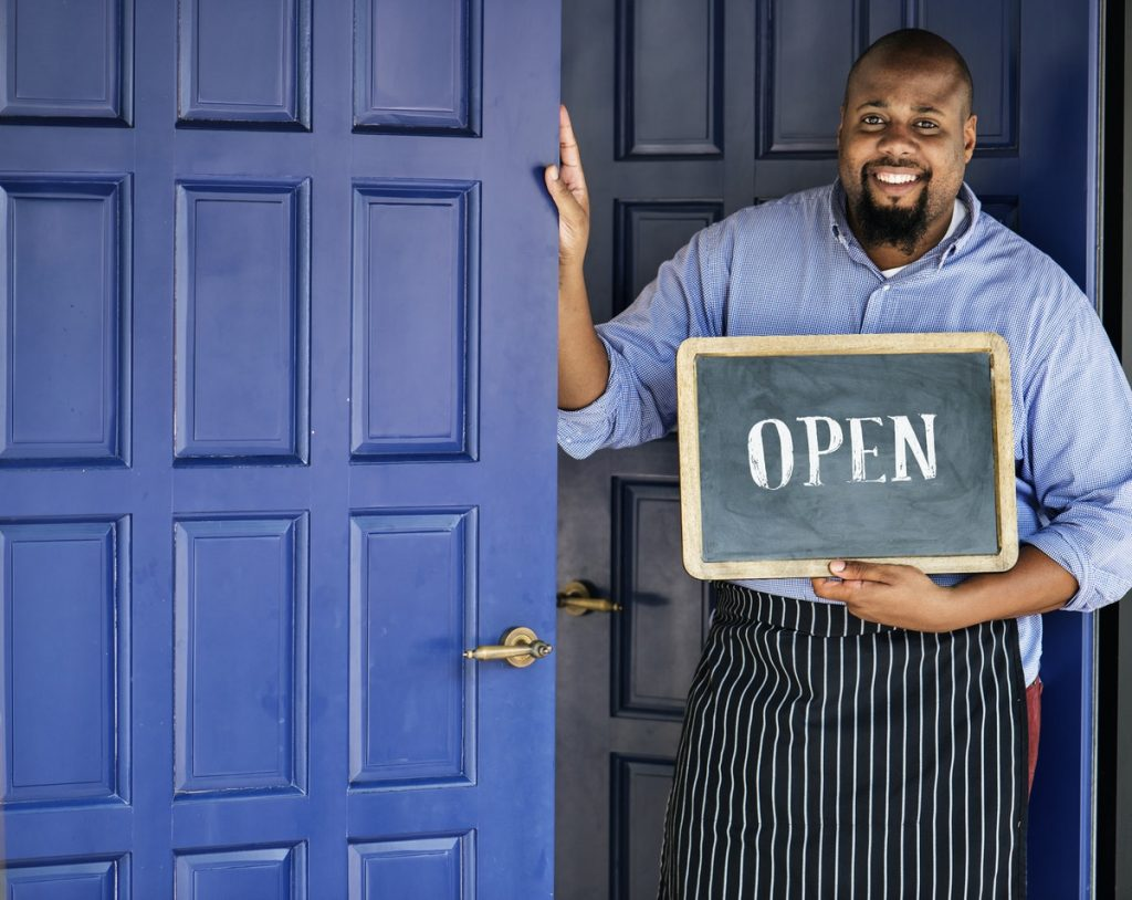 Shop owner holding open sign | 6-point step to creating a franchise