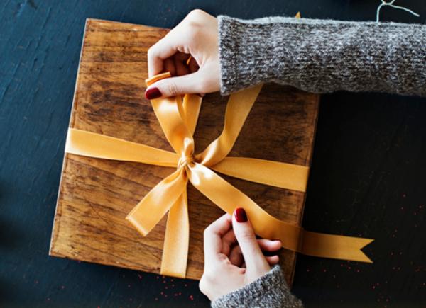 Hands wrapping present | TopCashback Signup Bonus