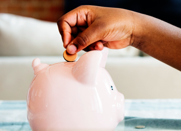 Child's hand putting coin into piggy bank | A penny saved in February 2019
