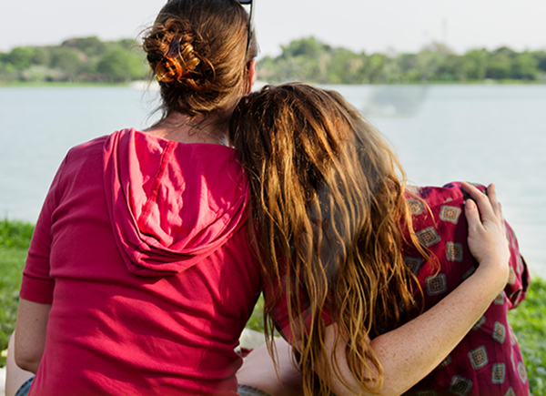 goHenry Review - keep your kids safe & teach them about money. Mother and daughter hugging at a picnic.